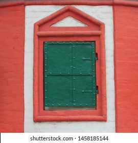 Colorful closed window shutter on house wall of old medieval style house. Locked window with retro green shutter on white and red building facade, close up view