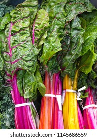 Colorful closeup market display of fresh organic rainbow chard, a flavorful, antioxidant leafy green vegetable packed with vitamins.