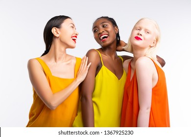 Colorful clothes. Beaming cheerful women with different skin color wearing bright colorful clothes