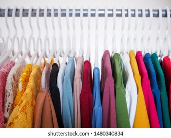 Colorful clothes with hangers on rails of clothesline in room.