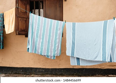Colorful Clothes Hanging to Dry on Old Street Galle Fort near Ancient Brown House. Sheet and Towel Dried after Washing near Window with Wooden Shutters on Village Alley of Sri Lanka