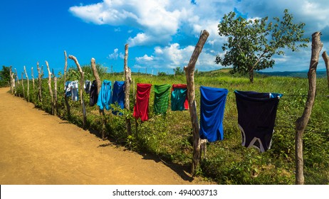 Colorful clothes hanging on clothesline to dry, along a dirt road in a village - Catanduanes, Philippines