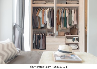 colorful clothes hanging on rail in wooden wardrobe