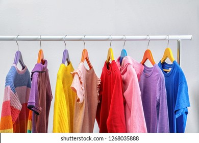 Colorful clothes hanging on wardrobe rack against light background