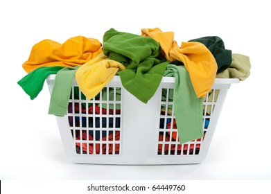 Colorful clothes in a laundry basket on white background. Green, yellow.
