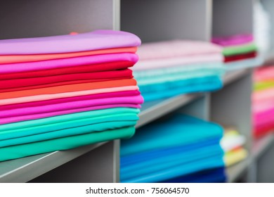 Colorful clothes on shelves in the shop.