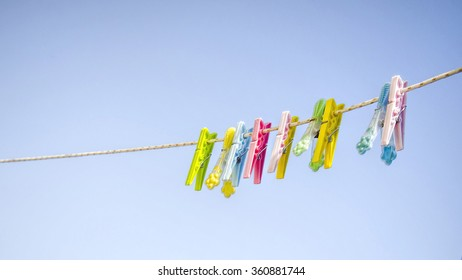 Colorful clothes pegs on a rope