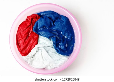 Colorful clothes washed with a basin with soap bubbles, close-up, top view
