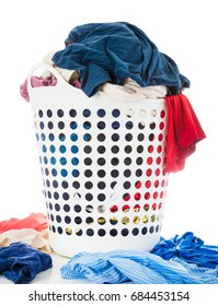 Colorful clothes in white laundry plastic clothes basket beside messy stack clothes on floor, Laundry and Housework concept, Isolated on white background.