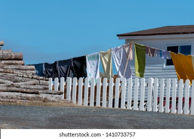 A colorful clothesline in a fenced yard with a white building and a pile of logs stacked under a blue sky. The clothesline contains towels and clothes. The white fence is in the foreground.