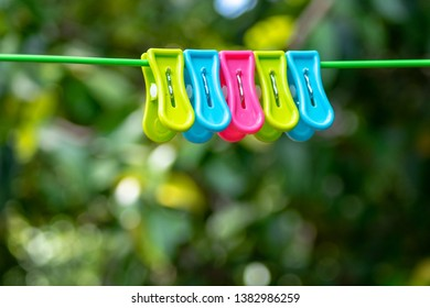 Colorful clothespin clothespins on the hangers. Plastic and wooden clothespins in different colors. And blur image of bokeh tree green and color background.
