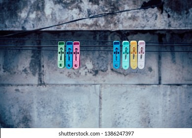 Colorful clothespin clothespins on the hangers with old wall