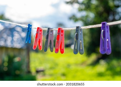 Colorful clothespins hang on the clothesline, line for clothes and linen on a blurred natural background on a sunny day. The concept of washing clothes and linen in nature.