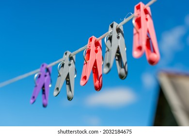 Colorful clothespins hang on the clothesline, line for clothes and linen on a blurred blue sky background on a sunny day. The concept of washing clothes and linen in nature.