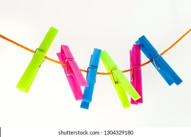 colorful clothespins on a rope on an isolated white background