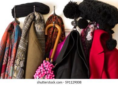 Colorful clothing, coats, hats and umbrella on coat hook – cold winter season