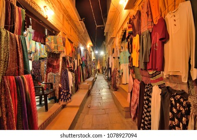 Colorful clothing items displayed by the shops in the streets at night in jaisalmer.