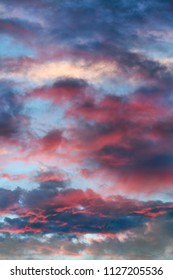 Colorful clouds clear to reveal a blue sky at sunrise.