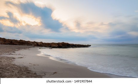Colorful clouds in the early morning just before sunrise. A bay with sandy beach for swimming near the Spanish town of Torrevieja. Soft waves through long exposure.
