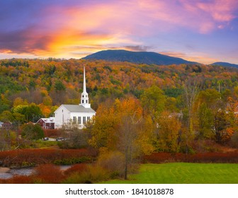 Colorful clouds and fall foliage surrounding Stowe Church in Vermont