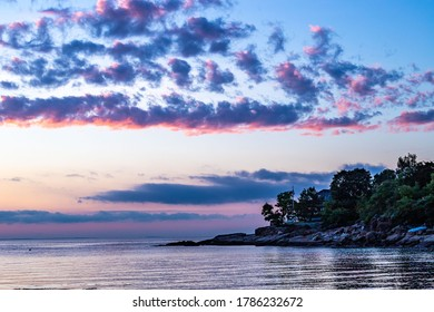 Colorful clouds glowing in the sky above the ocean during sunset.