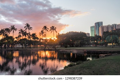 Colorful clouds and palm trees reflecting sunset onto the lagoon at Ala Moana Beach Park in Honolulu