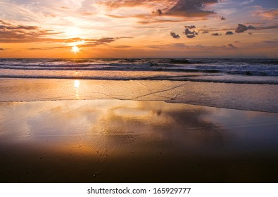 Colorful cloudy sunset at the beach with reflection - horizontal