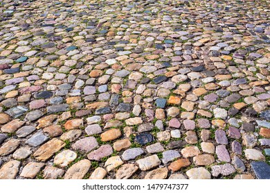 Colorful cobblestone pattern on old European cobbled street