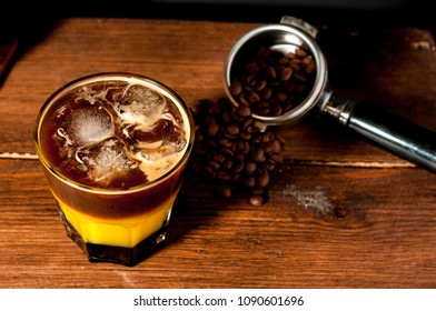 colorful cocktail of bumble or crazy bee with orange juice caramel syrup and espresso coffee in a glass beaker with ice cold summer cocktail on a wooden table coffee machine on the background
