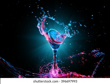 colorful cocktail in glass with splashes and lemon on dark background. Party club entertainment. Mixed light