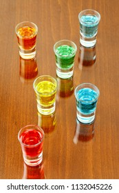 colorful cocktail shots on wooden surface