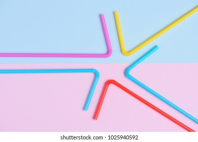 Colorful cocktail straws flat lay on blue and pink soft trendy pastel colored paper background with side copy space