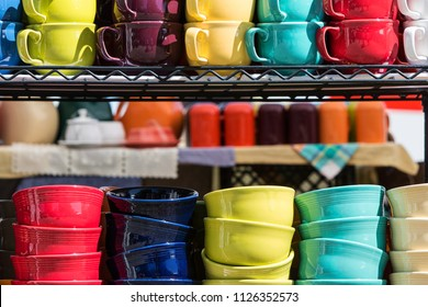 Colorful coffee mugs and bowls sit on shelf for sale at antique festival.