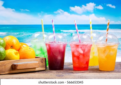 colorful cold drinks in plastic cups with ice and fresh fruits on the beach.