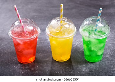 colorful cold drinks in plastic cups on dark background.