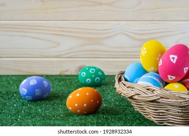 colorful color Easter egg in wooden basket on green grass closeup with copy space for text.use as happy easter holiday background.