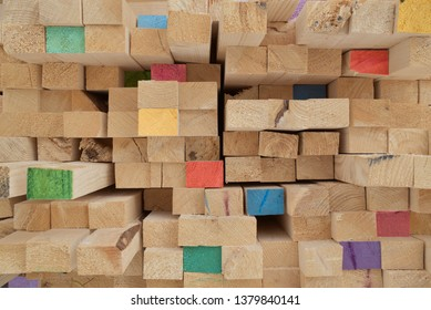 Colorful colored butt ends stacked logs long board wooden planks background wood board hardwood. Natural photo.