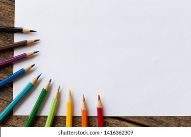 colorful colored pencil and white paper on wooden background