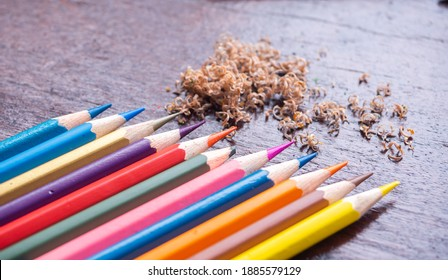 colorful colorpencil on wooden table in daylight, a broken pencil at the midle of shrarpened crayons. coloring wallpaper. education and creativity development for kids concept