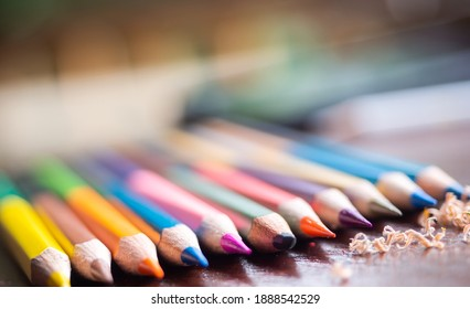 colorful colorpencil on wooden table in daylight, a broken pencil at the midle of sharpened crayons. coloring wallpaper. education and creativity development for kids concept