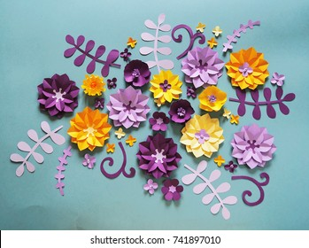Colorful composition of handmade paper on a blue background. Paper flower. A bright flower, a daisy, a rose, leaves on a branch, a curl.