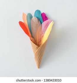 Colorful composition made of feathers and ice cream cone. MInimal boho style color concept. Flat lay summer food backgrund.