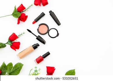 Colorful composition with red bright roses, lipstick, rimmel and woman accessories. Flat lay on white table, top view