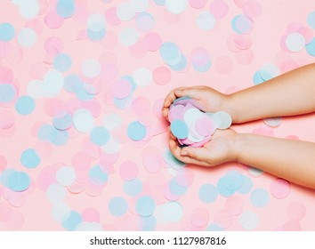 Colorful confetti background with child's hands holding confetti. Festival and bright. Top view, flat lay. Copy space for your text