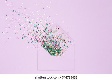 Colorful Confetti explosion from envelope on lilac background. Festive Cheerful greeting card. Shiny Gold stars and colored pebbles. Congratulations on holidays. Minimal, flat lay