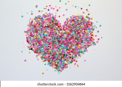 Colorful confetti in the form of a heart on a white background. Background, texture.