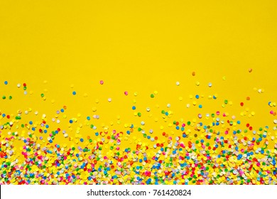 Colorful Confetti in front of orange Background.