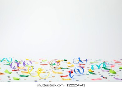 Colorful confetti and streamers on white background