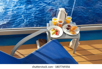 A colorful continental breakfast served on a balcony of a cruise ship at sea, with fruit, juice, breads and coffee.
