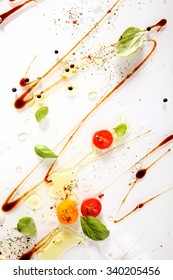 Colorful cooking ingredients abstract background with swirled soy sauce, pepper, halved cherry tomatoes and fresh green basil leaves on a white background